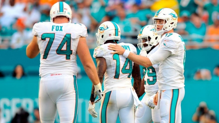 Sep 27, 2015; Miami Gardens, FL, USA; Miami Dolphins quarterback Ryan Tannehill (right) checks on Dolphins wide receiver Jarvis Landry (center) after a play during the first half against the Buffalo Bills at Sun Life Stadium. Mandatory Credit: Steve Mitchell-USA TODAY Sports