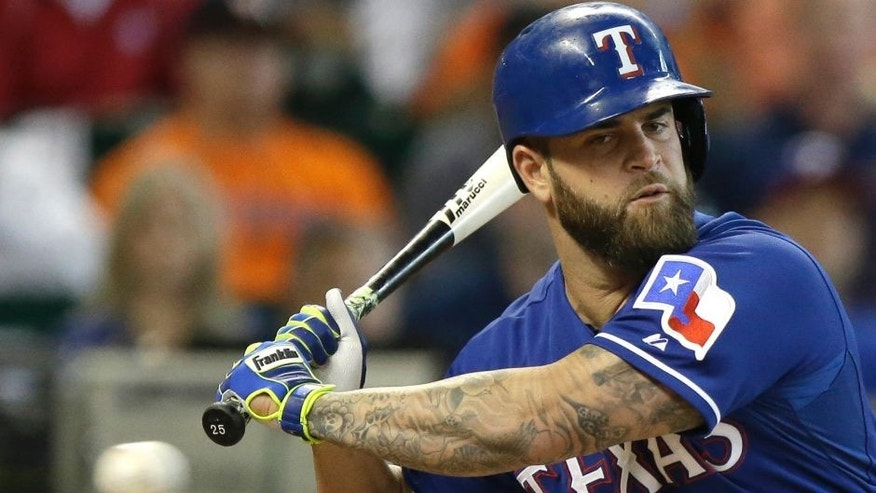 Texas Rangers' Mike Napoli keeps his eyes on the ball on his way to striking out against the Houston Astros in the first inning of a baseball game, Sunday, Sept. 27, 2015, in Houston. (AP Photo/Pat Sullivan)