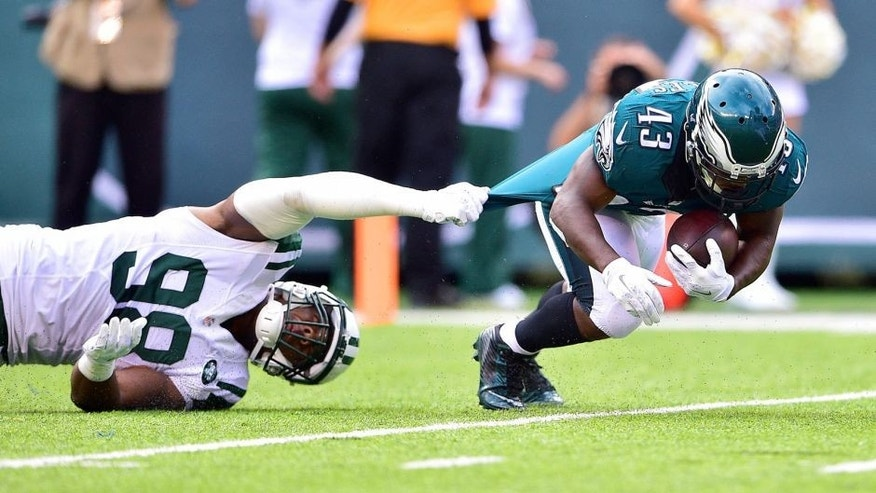 Sep 27, 2015; East Rutherford, NJ, USA; Philadelphia Eagles running back Darren Sproles (43) is taken down by New York Jets outside linebacker Quinton Coples (98) in the first half at MetLife Stadium. Mandatory Credit: Steven Ryan-USA TODAY Sports
