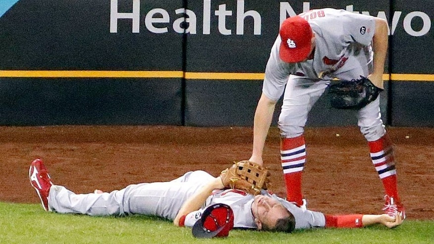 St. Louis Cardinals center fielder Peter Bourjos (8) checks teammate left fielder Stephen Piscotty after the two collided while catching a fly ball by Pittsburgh Pirates' Josh Harrison in the seventh inning of a baseball game in Pittsburgh, Monday, Sept. 28, 2015. Piscotty was driven off the field and taken to the hospital. (AP Photo/Gene J. Puskar)
