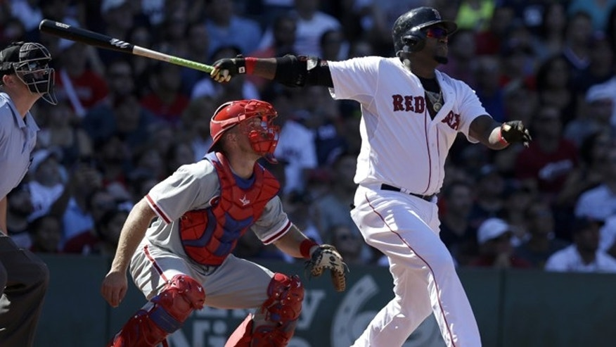 Boston Red Sox's David Ortiz, right, hits a sacrifice fly, allowing Mookie Betts to score, as Philadelphia Phillies catcher Erik Kratz, center, looks on in the second inning of a baseball game Sunday, Sept. 6, 2015, at Fenway Park, in Boston. The Red Sox won 6-2. (AP Photo/Steven Senne)