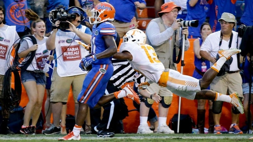 Florida wide receiver Antonio Callaway , left, crosses the goal line past Tennessee defensive back Malik Foreman, right, to score the game winning touchdown on a 63-yard pass play during the final minutes of an NCAA college football game, Saturday, Sept. 26, 2015, in Gainesville, Fla. Florida won 28-27. (AP Photo/John Raoux)