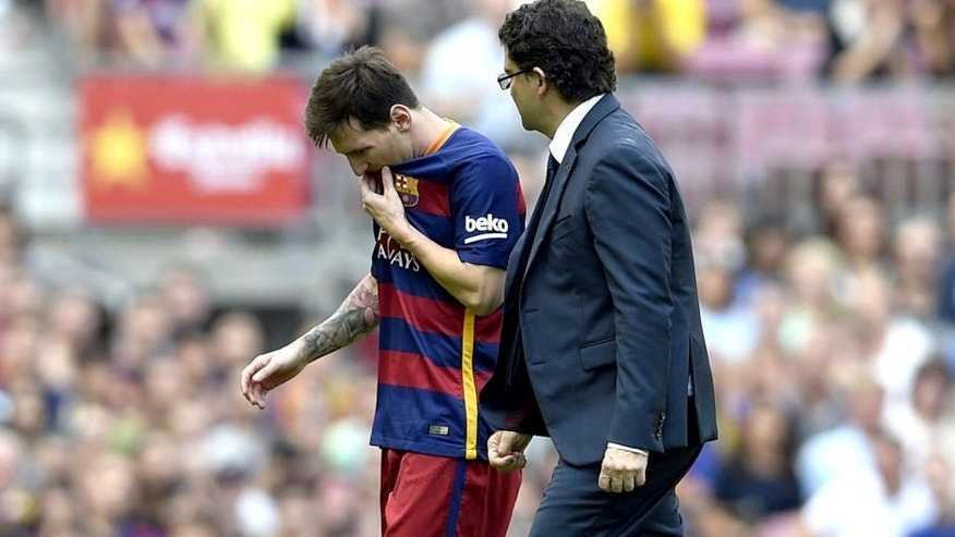 Barcelona's Argentinian forward Lionel Messi (L) leaves the picht after being injured during the Spanish league football match FC Barcelona v UD Las Palmas at the Camp Nou stadium in Barcelona on September 26, 2015. AFP PHOTO / LLUIS GENE (Photo credit should read LLUIS GENE/AFP/Getty Images)