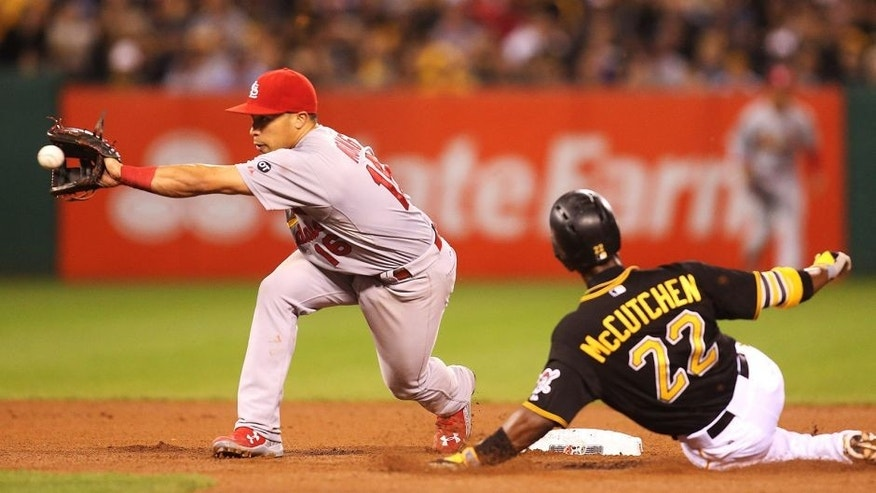 Sep 28, 2015; Pittsburgh, PA, USA; St. Louis Cardinals second baseman Kolten Wong (16) takes a late throw as Pittsburgh Pirates center fielder Andrew McCutchen (22) steals second base during the seventh inning at PNC Park. Mandatory Credit: Charles LeClaire-USA TODAY Sports
