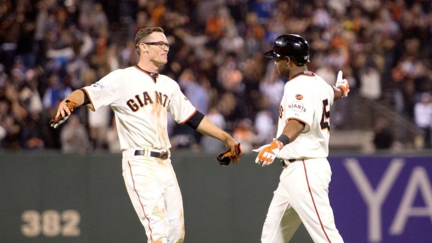 September 28, 2015; San Francisco, CA, USA; San Francisco Giants second baseman Kelby Tomlinson (37, left) congratulates pinch hitter Alejandro De Aza (45, right) for hitting the game-winning sacrifice fly during the 12th inning against the Los Angeles Dodgers at AT&T Park. The Giants defeated the Dodgers 3-2 in 12 innings. Mandatory Credit: Kyle Terada-USA TODAY Sports