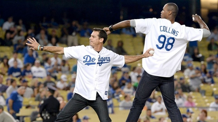 LOS ANGELES, CA - SEPTEMBER 27: NBA player Jason Collins and former Major League Baseball player Billy Beane throw out the ceremonial first pitch before the game between the Colorado Rockies and the Los Angeles Dodgers at Dodger Stadium on September 27, 2013 in Los Angeles, California. (Photo by Harry How/Getty Images)