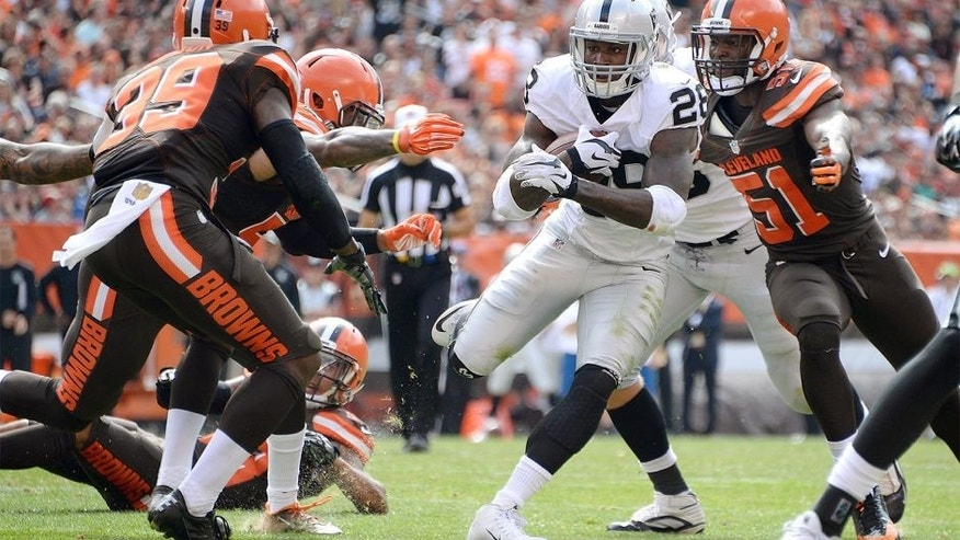 CLEVELAND, OH - SEPTEMBER 27: Latavius Murray #28 of the Oakland Raiders carries the ball between the defense of Tashaun Gipson #39 and Barkevious Mingo #51 of the Cleveland Browns during the second quarter at FirstEnergy Stadium on September 27, 2015 in Cleveland, Ohio. (Photo by Jason Miller/Getty Images)