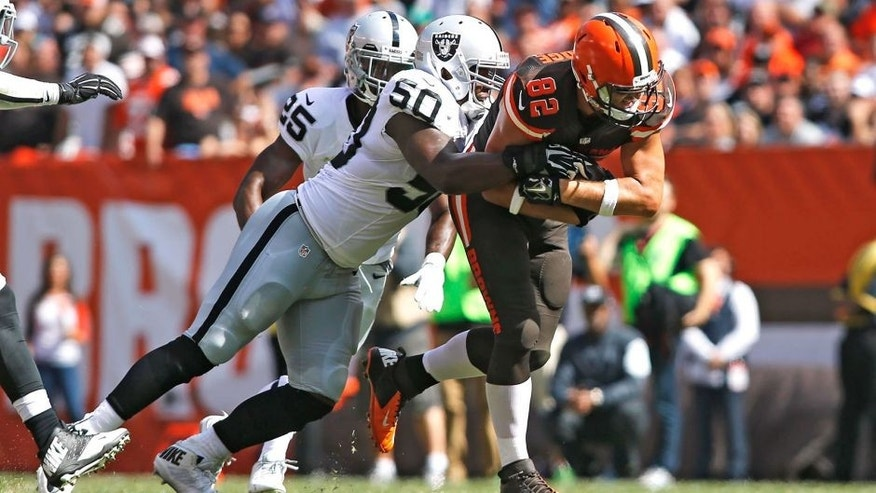 Sep 27, 2015; Cleveland, OH, USA; Cleveland Browns tight end Gary Barnidge (82) gets tackled by Oakland Raiders middle linebacker Curtis Lofton (50) at FirstEnergy Stadium. The Raiders defeated the Browns 27-20. Mandatory Credit: Scott R. Galvin-USA TODAY Sports