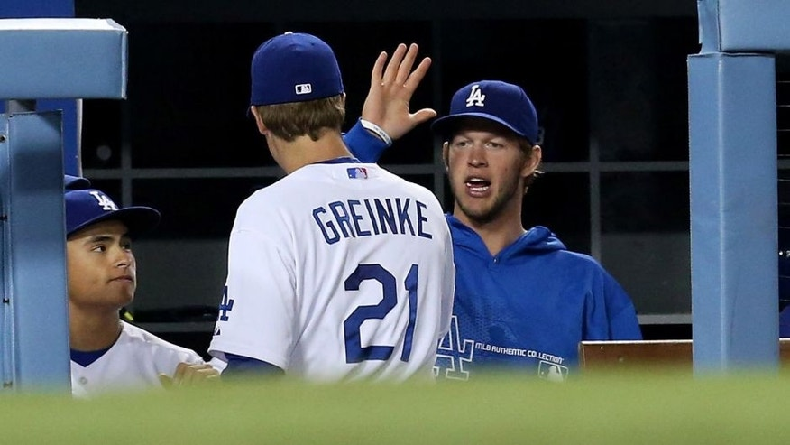 LOS ANGELES, CA - MAY 15: Zack Greinke #21 of the Los Angeles Dodgers is greeted in the dugout by Clayton Kershaw#22 after being relieved in the sixth inning of the game against the Washington Nationals at Dodger Stadium on May 15, 2013 in Los Angeles, California. (Photo by Stephen Dunn/Getty Images)