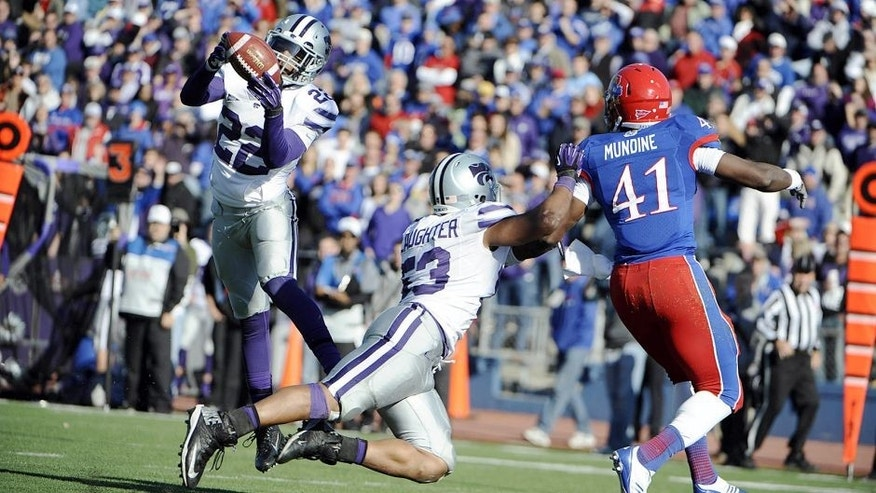 Nov 30, 2013; Lawrence, KS, USA; Kansas State Wildcats defensive back Dante Barnett (22) intercepts a pass intended for Kansas Jayhawks tight end Jimmay Mundine (41) as linebacker Blake Slaughter (53) defends in the second half at Memorial Stadium. Kansas State won the game 31-10. Mandatory Credit: John Rieger-USA TODAY Sports