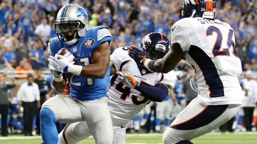 DETROIT, MI - SEPTEMBER 27: Ameer Abdullah #21 of the Detroit Lions scores a third quarter touchdown while being defended by the Denver Broncos at Ford Field on September 27, 2014 in Detroit, Michigan. (Photo by Leon Halip/Getty Images)