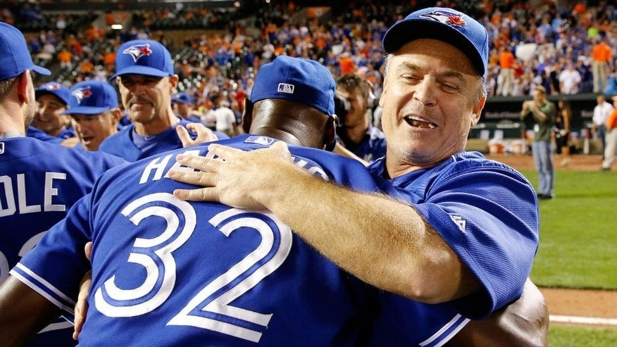 Toronto Blue Jays manager John Gibbons, right, celebrates with relief pitcher LaTroy Hawkins after winning the first baseball game of a doubleheader against the Baltimore Orioles, Wednesday, Sept. 30, 2015, in Baltimore. Toronto won 15-2 to clinch the American League East. (AP Photo/Patrick Semansky)