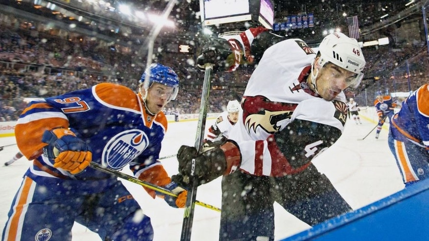 Arizona Coyotes' Jordan Martinook, right, and Edmonton Oilers' Connor McDavid (97) battle in the corner during the first period of a preseason NHL hockey game in Edmonton, Alberta, Tuesday, Sept. 29, 2015. (Jason Franson/The Canadian Press via AP) MANDATORY CREDIT