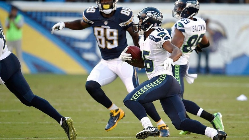 Seattle Seahawks wide receiver Tyler Lockett, second from right, returns a punt for a touchdown against the San Diego Chargers during the first half of a preseason NFL football game Saturday, Aug. 29, 2015, in San Diego. (AP Photo/Denis Poroy)