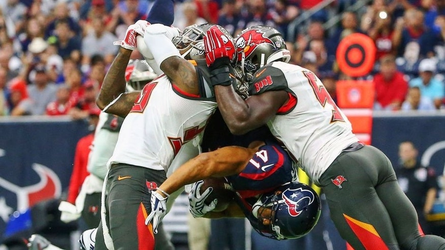 Sep 27, 2015; Houston, TX, USA; Houston Texans running back Jonathan Grimes (41) is tackled by Tampa Bay Buccaneers defensive back D.J. Swearinger (left) and outside linebacker Lavonte David (right) during the first quarter at NRG Stadium. Mandatory Credit: Kevin Jairaj-USA TODAY Sports
