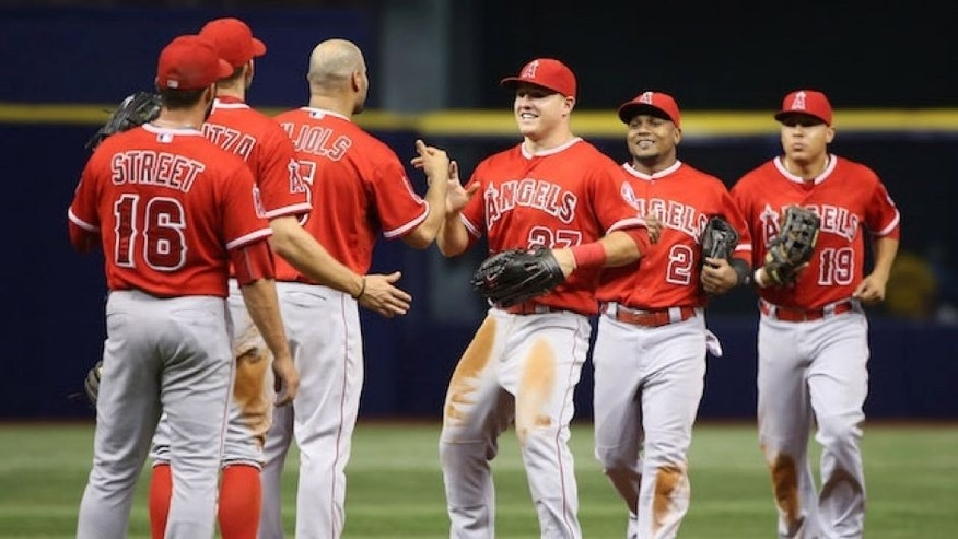 Jun 11, 2015; St. Petersburg, FL, USA; Los Angeles Angels center fielder Mike Trout (27) and first baseman Albert Pujols (5) celebrate with teammates after defeating the Tampa Bay Rays 6-2 at Tropicana Field. Mandatory Credit: Kim Klement-USA TODAY Sports