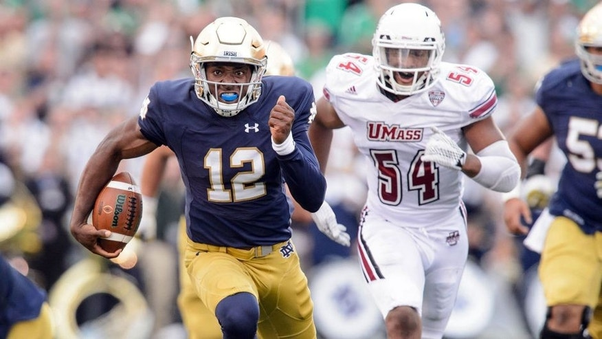 Sep 26, 2015; South Bend, IN, USA; Notre Dame Fighting Irish quarterback Brandon Wimbush (12) runs for a touchdown in the third quarter against the Massachusetts Minutemen at Notre Dame Stadium. Notre Dame won 62-27. Mandatory Credit: Matt Cashore-USA TODAY Sports