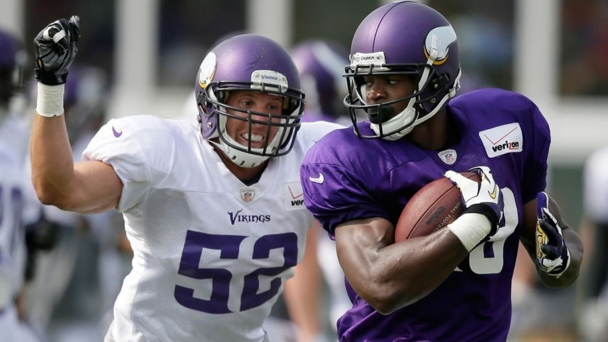 <p>Minnesota Vikings running back Adrian Peterson, right, runs from outside linebacker Chad Greenway during an NFL football training camp practice, Wednesday, July 30, 2014, in Mankato, Minn. (AP Photo/Charlie Neibergall)</p>