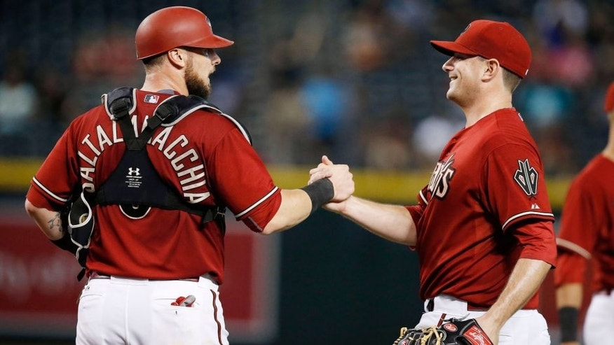 Arizona Diamondbacks' Daniel Hudson, right, shakes hands with catcher Jarrod Saltalamacchia, left, after the final out in the ninth inning of a baseball game against the Colorado Rockies Wednesday, Sept. 30, 2015, in Phoenix. The Diamondbacks defeated the Rockies 3-1. (AP Photo/Ross D. Franklin)
