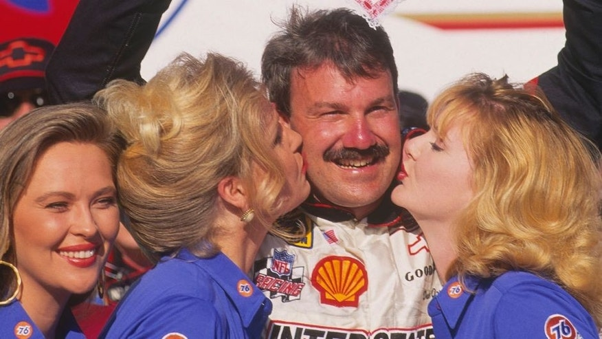 "DAYTONA BEACH, FL - FEBRUARY 14: Dale Jarrett raises an ""I Luv Daytona 500"" sign shaped like a heart as two blonde ""76"" girls give him on a kiss on the cheek to celebrate his winning the Daytona 500 at Daytona Speedway on February 14, 1993 in Daytona Beach, Florida. (Photo by Focus on Sport/Getty Images)"