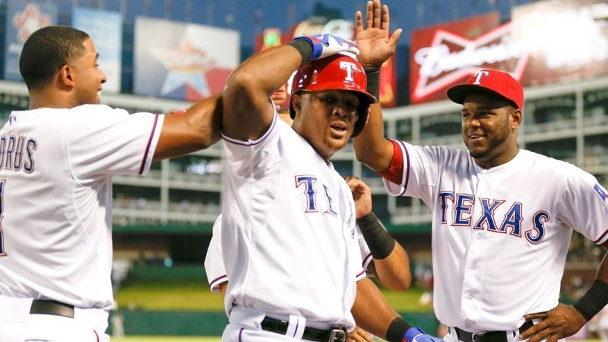 The Texas Rangers' Adrian Beltre, center, celebrates his two-run home run with Elvis Andrus, left, and Hanser Alberto against the Detroit Tigers during the first inning on Wednesday, Sept. 30, 2015, at Globe Life Park in Arlington, Texas. (Jim Cowsert/Fort Worth Star-Telegram/TNS via Getty Images)