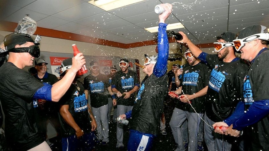 Sep 30, 2015; Baltimore, MD, USA; Toronto Blue Jays third baseman Josh Donaldson (center) celebrates winning the A.L. East division with his teammates after game two of a double header in the visiting locker room at Oriole Park at Camden Yards. The Toronto Blue Jays clinched the division after game one of the double header. Mandatory Credit: Tommy Gilligan-USA TODAY Sports