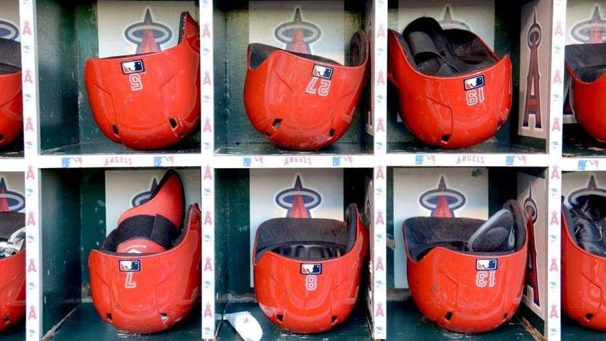 Sep 19, 2014; Anaheim, CA, USA; General view of Los Angeles Angels helmets of Albert Pujols (5), Mike Trout (27), Efren Navarro (19), Collin Cowgill (7), John McDonald (8) and Luis Jimenez (13) in the dugout before the game against the Texas Rangers at Angel Stadium of Anaheim. Mandatory Credit: Kirby Lee-USA TODAY Sports