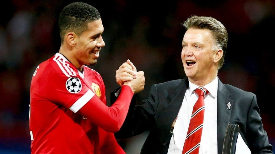 MANCHESTER, ENGLAND - SEPTEMBER 30: Louis van Gaal manager of Manchester United celebrates victory with winning goalscorer Chris Smalling in the UEFA Champions League Group B match between Manchester United FC and VfL Wolfsburg at Old Trafford on September 30, 2015 in Manchester, United Kingdom. (Photo by Dean Mouhtaropoulos/Getty Images)