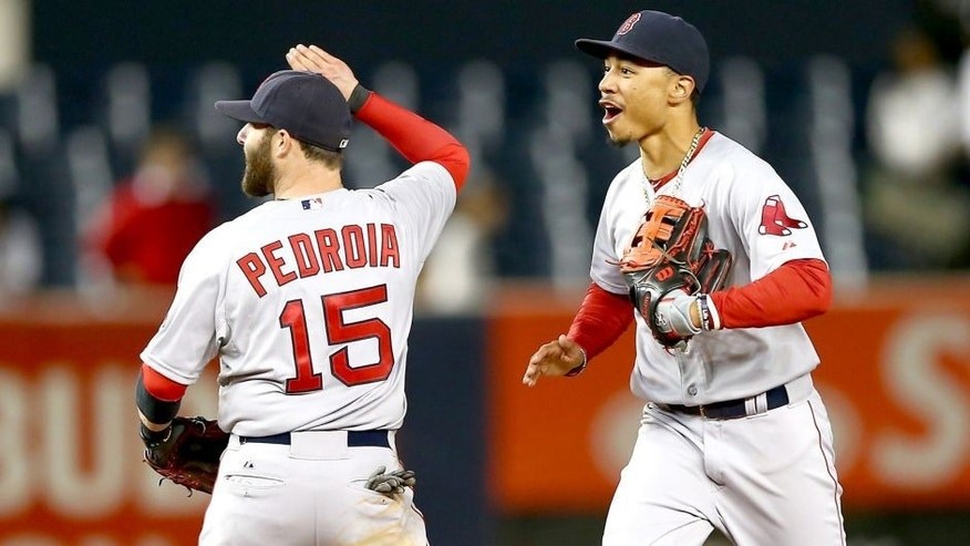 NEW YORK, NY - SEPTEMBER 30: Dustin Pedroia #15 and Mookie Betts #50 of the Boston Red Sox celebrate the win over the New York Yankees on September 30, 2015 at Yankee Stadium in the Bronx borough of New York City.The Boston Red Sox defeated the New York Yankees 9-5 in 11 innings. (Photo by Elsa/Getty Images)