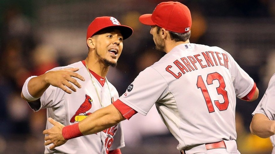 Sep 30, 2015; Pittsburgh, PA, USA; St. Louis Cardinals center fielder Jon Jay (19) and third baseman Matt Carpenter (13) celebrate after defeating the Pittsburgh Pirates to clinch the National League Central Division Championship at PNC Park. The Cardinals won 11-1. Mandatory Credit: Charles LeClaire-USA TODAY Sports