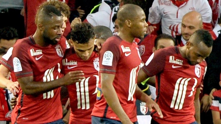 ALTERNATIVE CROP Lille's French midfielder Sofiane Boufal (C) celebrates with teammates after scoring a goal during the French L1 football match between Lille and Montpellier on October 2, 2015 at the Pierre Mauroy stadium in Villeneuve d'Ascq, northern France. AFP PHOTO / DENIS CHARLET (Photo credit should read DENIS CHARLET/AFP/Getty Images)