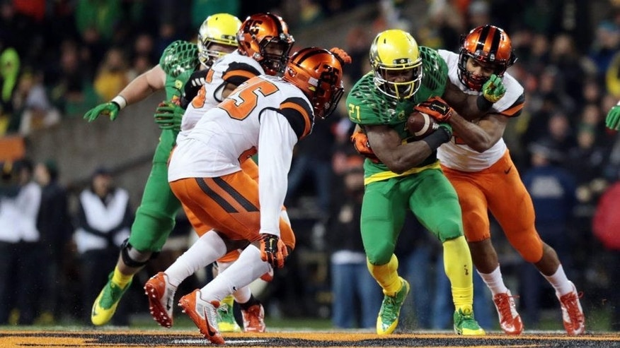 Nov 29, 2014; Corvallis, OR, USA; Oregon State Beavers linebacker D.J. Alexander (4) reaches out to tackle Oregon Ducks running back Royce Freeman (21) at Reser Stadium. Mandatory Credit: Scott Olmos-USA TODAY Sports