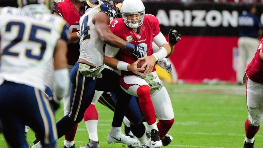 Nov 9, 2014; Glendale, AZ, USA; Arizona Cardinals quarterback Carson Palmer (3) is sacked by St. Louis Rams defensive end Robert Quinn (94) and defensive tackle Aaron Donald (99) during the first half at University of Phoenix Stadium. Mandatory Credit: Matt Kartozian-USA TODAY Sports