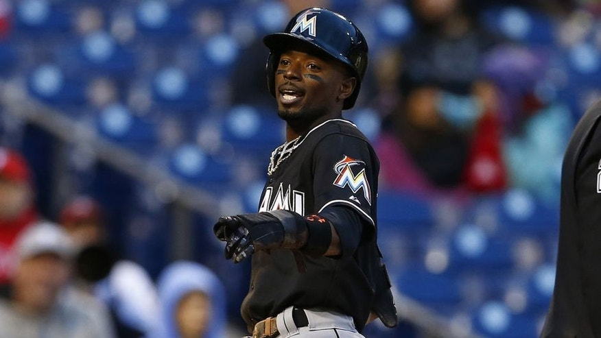 Miami Marlins Dee Gordon scores after stealing third base and advancing on a throwing error by Philadelphia Phillies catcher Carlos Ruiz, not in picture, during the sixth inning of the first game of a baseball doubleheader, Saturday, Oct. 3, 2015, in Philadelphia. (AP Photo/Rich Schultz)