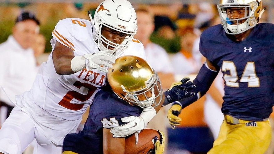 SOUTH BEND, IN - SEPTEMBER 05: Kris Boyd #2 of the Texas Longhorns tackles and dislodges the helmet of Jaylon Smith #9 of the Notre Dame Fighting Irish during the fourth quarter at Notre Dame Stadium on September 5, 2015 in South Bend, Indiana. The Notre Dame Fighting Irish won 38-3. (Photo by Jon Durr/Getty Images)