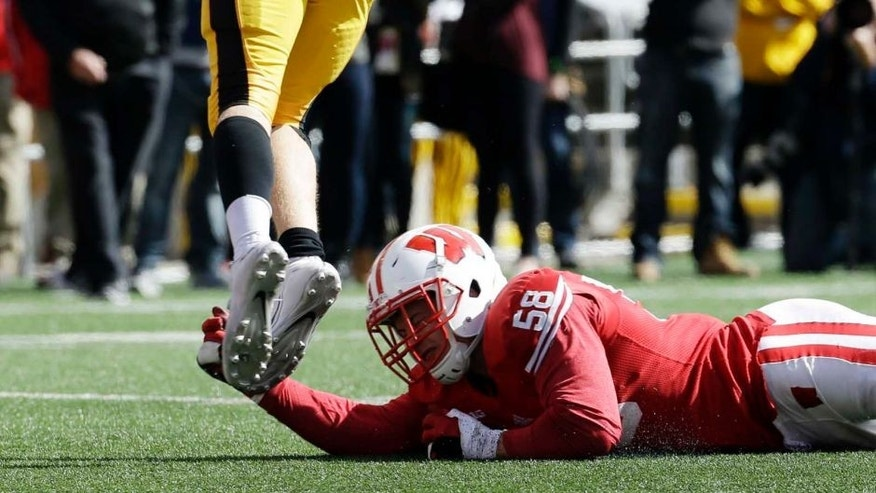 Iowa quarterback C.J. Beathard is tripped by Wisconsin's Joe Schobert as he throws during the second half of an NCAA college football game Saturday, Oct. 3, 2015, in Madison, Wis.