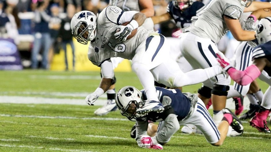 Oct 18, 2014; Provo, UT, USA; Nevada Wolf Pack running back Don Jackson (6) is tackled by Brigham Young Cougars defensive back Kai Nacua (12) during the second quarter at Lavell Edwards Stadium. Mandatory Credit: Chris Nicoll-USA TODAY Sports