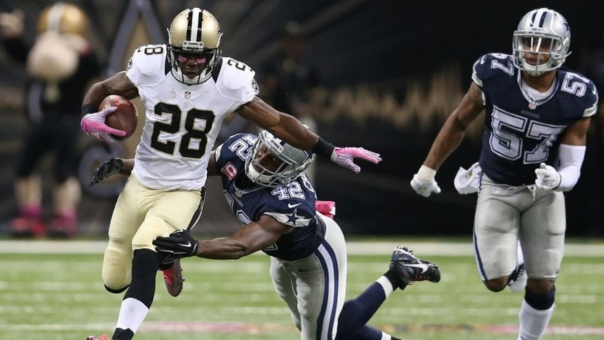 Oct 4, 2015; New Orleans, LA, USA; New Orleans Saints running back C.J. Spiller (28) breaks the tackle of Dallas Cowboys strong safety Barry Church (42) to score the game-winning 80-yard touchdown in overtime at Mercedes-Benz Superdome. The Saints won 26-20. Mandatory Credit: Chuck Cook-USA TODAY Sports