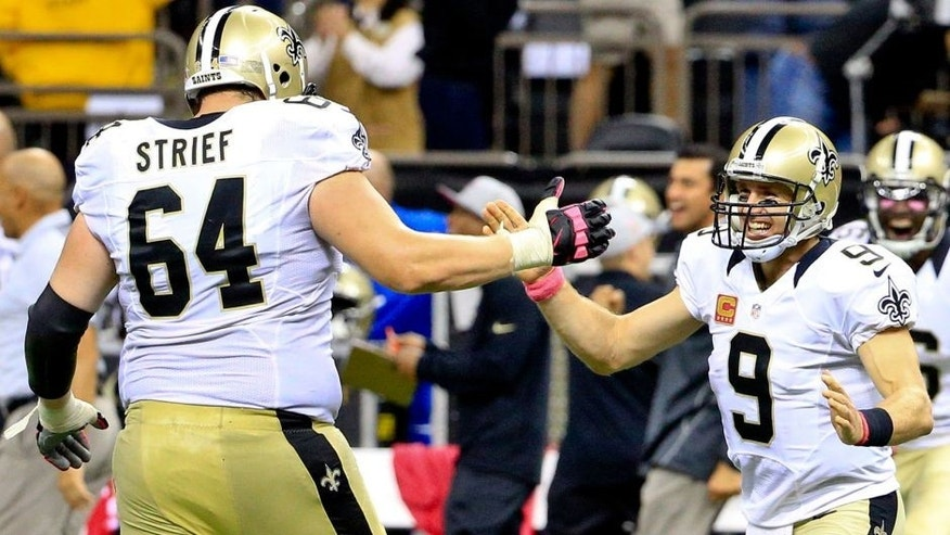 Oct 4, 2015; New Orleans, LA, USA; New Orleans Saints quarterback Drew Brees (9) and tackle Zach Strief (64) celebrates following an 80 yard game winning touchdown pass during overtime against the Dallas Cowboys at the Mercedes-Benz Superdome. The Saints won 26-20. The touchdown pass by Brees was the 400th touchdown pass of his career. Mandatory Credit: Derick E. Hingle-USA TODAY Sports