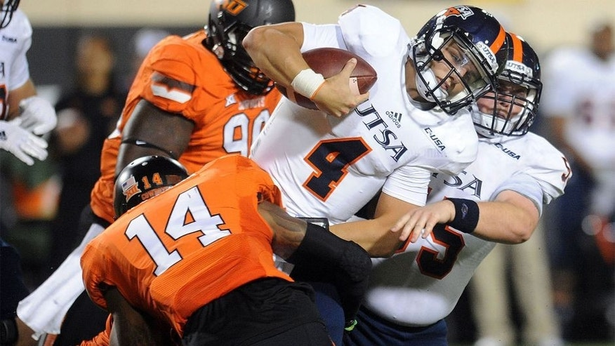 Sep 13, 2014; Stillwater, OK, USA; UTSA Roadrunners quarterback Blake Bogenschutz (4) carries the ball while being tackled by Oklahoma State Cowboys linebacker Josh Furman (14) during the fourth quarter at Boone Pickens Stadium. Mandatory Credit: Mark D. Smith-USA TODAY Sports