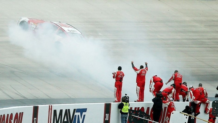 DOVER, DE - OCTOBER 04: Kevin Harvick, driver of the #4 Budweiser/Jimmy John's Chevrolet, celebrates with a burnout in front of his crew after winning the NASCAR Sprint Cup Series AAA 400 at Dover International Speedway on October 4, 2015 in Dover, Delaware. (Photo by Patrick Smith/Getty Images)
