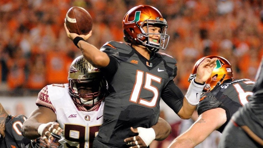 <p>Nov 15, 2014; Miami Gardens, FL, USA; Miami Hurricanes quarterback Brad Kaaya (15) is hit by Florida State Seminoles defensive end Rick Leonard (98) as he throws as the Seminoles beat the Hurricanes 30-26 at Sun Life Stadium. Mandatory Credit: David Manning-USA TODAY Sports</p>