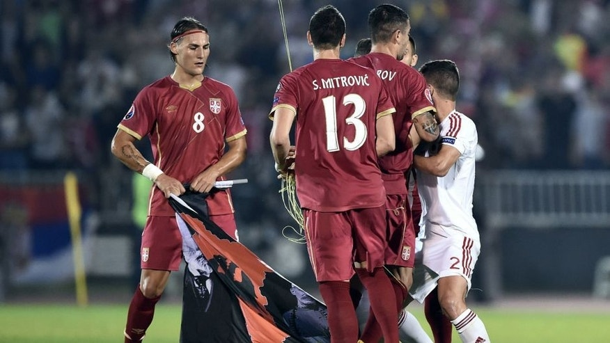 Serbia's midfielder Nemanja Gudelj (L) holds a flag with Albanian national symbols pulled down by Serbia's defender Stefan Mitrovic (C) from a remotely operated drone flown over the pitch during the EURO 2016 group I football match between Serbia and Albania in Belgrade on October 14, 2014. AFP PHOTO / ANDREJ ISAKOVIC (Photo credit should read ANDREJ ISAKOVIC/AFP/Getty Images)