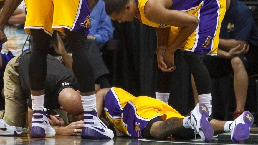 <p>Teammates look over Los Angeles Lakers guard D'Angelo Russell, center, after crashing to the ground against the Utah Jazz during the first half of an NBA preseason basketball game, Tuesday, Oct. 6, 2015, in Honolulu. (AP Photo/Marco Garcia)</p>