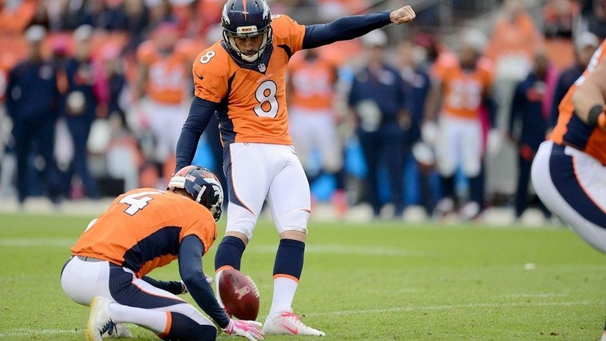 Oct 4, 2015; Denver, CO, USA; Denver Broncos kicker Brandon McManus (8) kicks the go ahead field goal as punter Britton Colquitt (4) holds late in the fourth quarter against the Minnesota Vikings at Sports Authority Field at Mile High. The Broncos defeated the Vikings 23-20. Mandatory Credit: Ron Chenoy-USA TODAY Sports