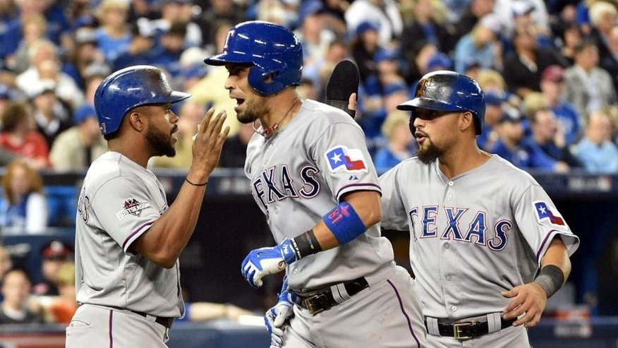 Oct 8, 2015; Toronto, Ontario, CAN; Texas Rangers catcher Robinson Chirinos (middle) celebrates with teammates Delino DeShields (left) and Rougned Odor (right) after hitting a two-run home run against the Toronto Blue Jays in the fifth inning in game one of the ALDS at Rogers Centre. Mandatory Credit: Nick Turchiaro-USA TODAY Sports