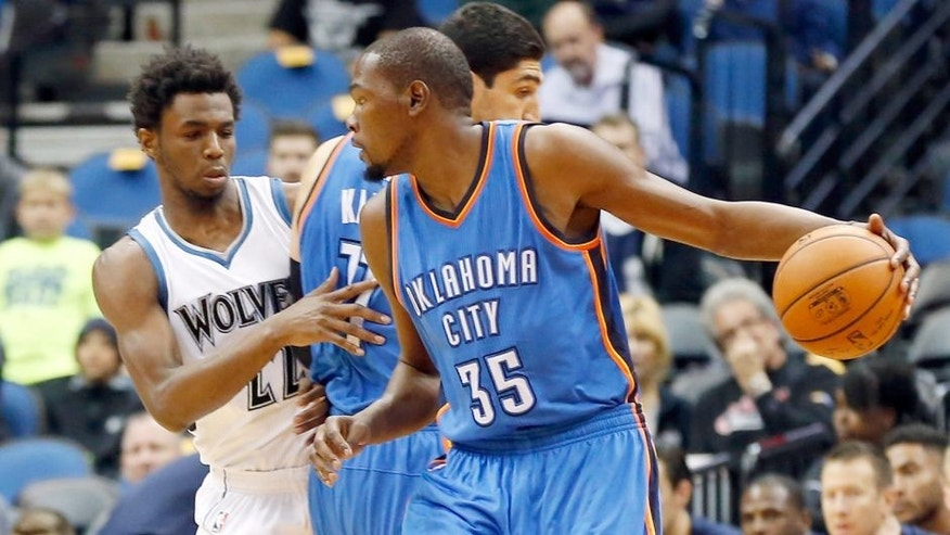 Oklahoma City Thunder's Kevin Durant, right, drives as Enes Kanter sets a pick on Minnesota Timberwolves' Andrew Wiggins, left, in the first half of an NBA preseason basketball game Wednesday, Oct. 7, 2015, in Minneapolis. (AP Photo/Jim Mone)