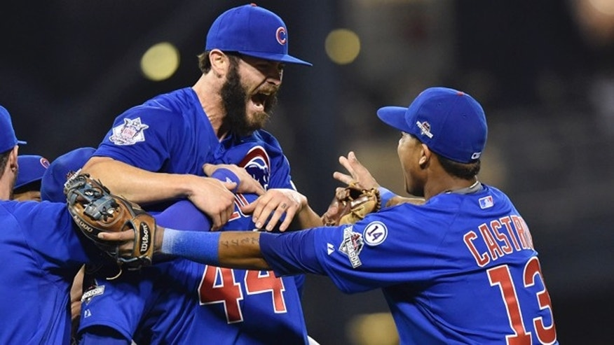 Chicago Cubs first baseman Anthony Rizzo, (44), holds Chicago Cubs starting pitcher Jake Arrieta as shortstop Starlin Castro (13) joins in the celebration after they defeated the Pittsburgh Pirates in the National League wild card baseball game 4-0, Wednesday, Oct. 7, 2015, in Pittsburgh. The Cubs advance to play the St. Louis Cardinals in the National League Division Series. (AP Photo/Don Wright)