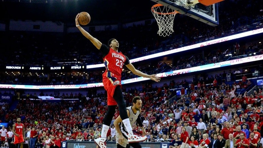 Apr 15, 2015; New Orleans, LA, USA; New Orleans Pelicans forward Anthony Davis (23) dunks over San Antonio Spurs forward Marco Belinelli (3) during the first quarter of a game at the Smoothie King Center. Mandatory Credit: Derick E. Hingle-USA TODAY Sports