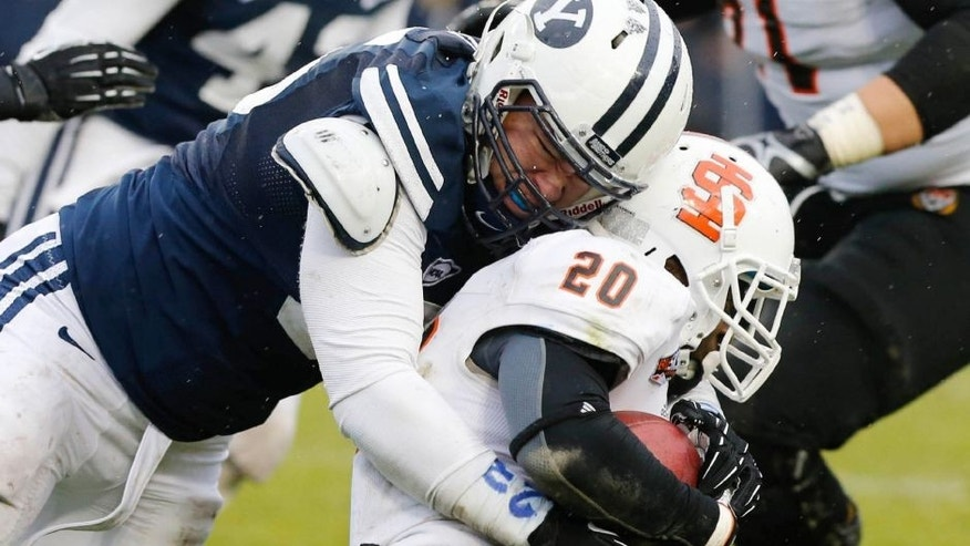 Nov 16, 2013; Provo, UT, USA; Idaho State Bengals running back Aaron Prier (20) is tackled by Brigham Young Cougars defensive lineman Logan Taele (95) during the third quarter at Lavell Edwards Stadium. BYU won 59-13. Mandatory Credit: Chris Nicoll-USA TODAY Sports.